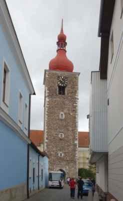 Chtěly jsme také nakouknout do kostela sv. Jana Křtitele, ale zrovna se tu formoval svatební špalír, tak jsme se dostaly jen ke gotické věži před kostelem. Původní věž je z roku 1497 a sloužila na obranu města. Z toho důvodu byl vstup do věže umístěný ve výšce 7 m, ke kterému vedlo dřevěné schodiště. V případě ohrožení bylo možné jej lehce odstranit. Od paty až po kříž na vrcholu báně je věž vysoká 50,3 m.