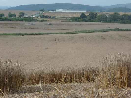 Snímek ze středu kruhu směrem severním. Na obzoru silnice E461 (1/43), vpravo od ní pak elektrotechnická továrna ALPS